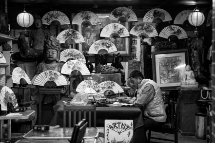 An artisan paints a paper fan in his workshop